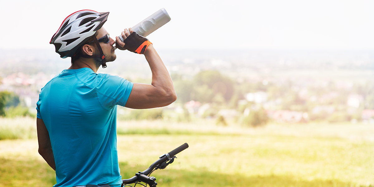 Photo of male cyclist taking a break to drink from a water bottle