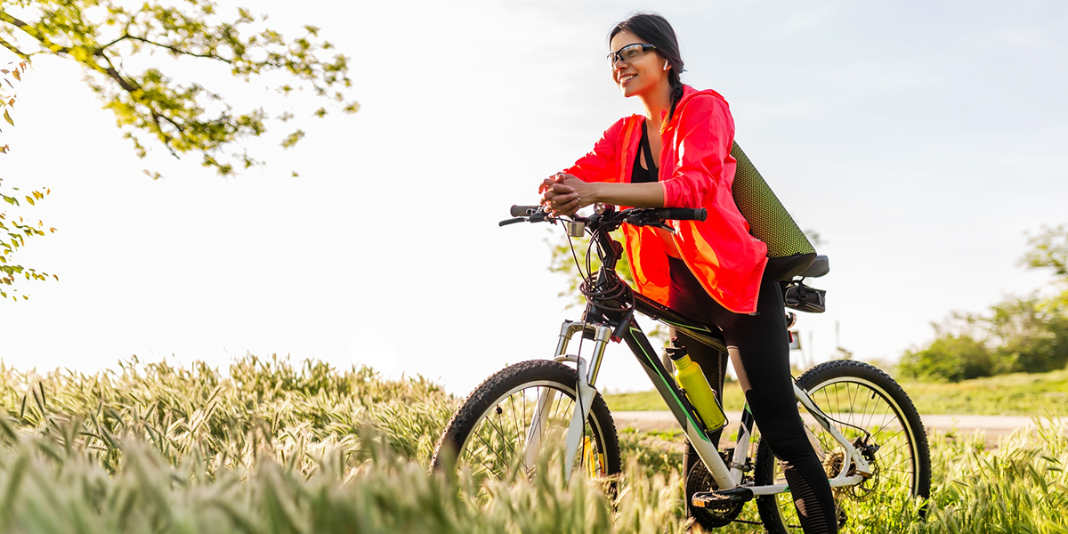Photo of a woman on a bicycle wearing active wear and eye protection.
